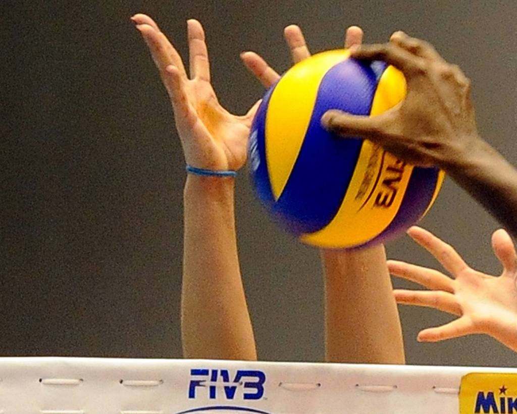 A volleyball and hands